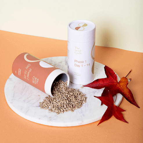 Two canisters 'of The Seed Cycle product on a circular marble tray. One of the canisters is laying on it's side with seed pouring out. There are two Autumn leaves sitting next to the packaging, which is on an orange and creamy yellow backdrop. The Seed Cycle Subscription.
