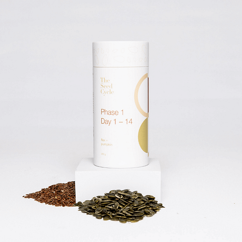 A canister of Phase 1 of The Seed Cycle product is standing on a small white block. Next to the block are two piles of seeds.