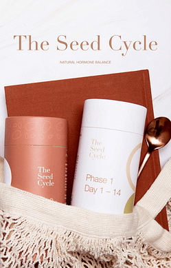 """A string shopping bag is laying on a kitchen benctop. Poking out of the bag is a red book, a gold spoon and two canisters of The Seed Cycle products. The text overlay reads - """"The Seed Cycle"""" in large letters, with the sub-heading """"Natural Hormone Balance""""."""